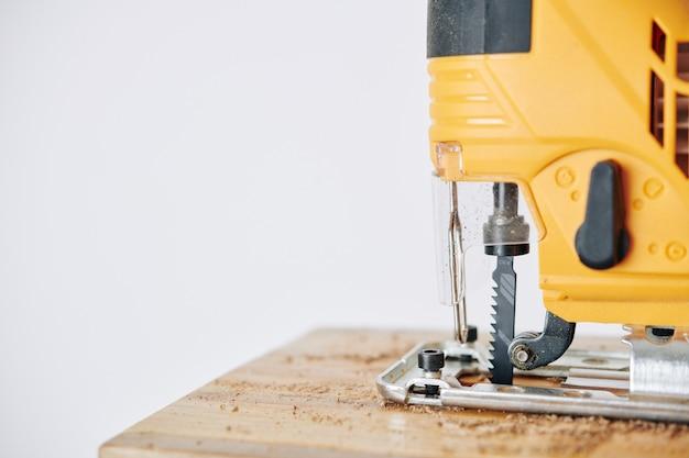 Elektrische decoupeerzaag die houten blok snijdt