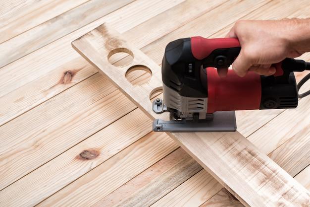 Elektrische decoupeerzaag in mannenhand. verwerking van werkstuk op lichtbruine houten tafel.