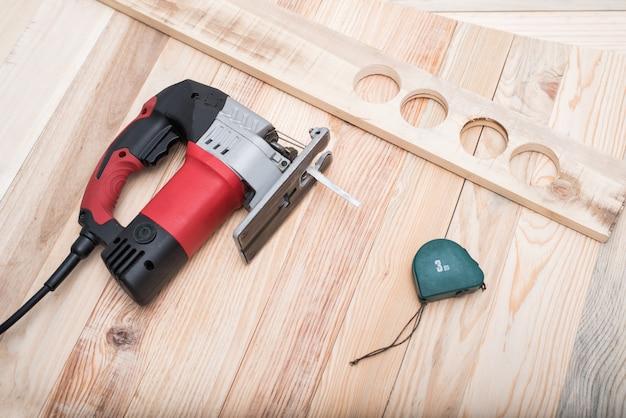 Elektrische decoupeerzaag, meetlint en werkstuk liggend op een lichtbruine houten tafel. houtbewerking. detailopname
