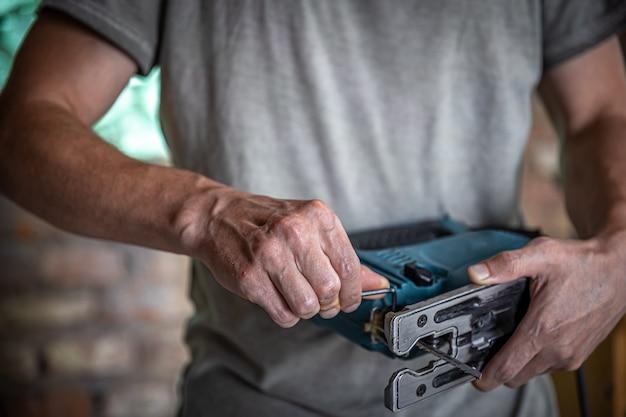 Elektrische decoupeerzaag met een zaag voor hout in handen van timmerman.