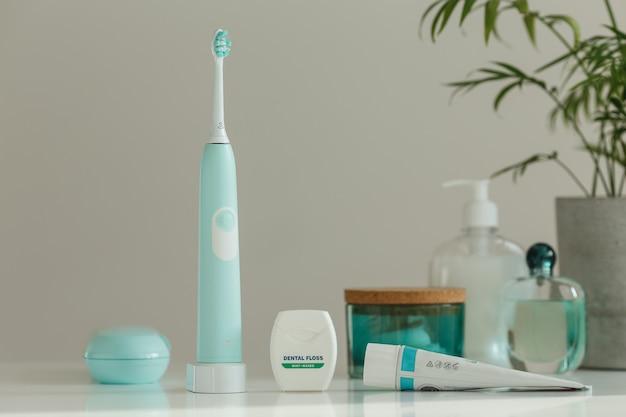 Elektrische draadloze ultrasone tandenborstel met tandzijde die zich in lichte badkamers bevinden
