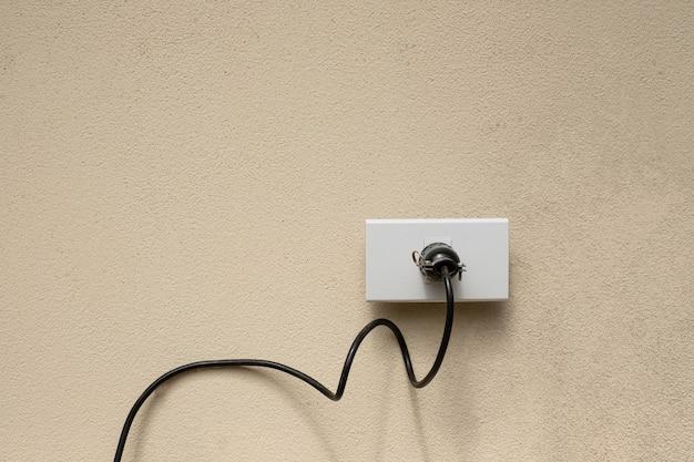 Elektrische draadstopcontactdoos op de betonnen muurachtergrond