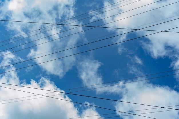 Elektrische draden tegen blauwe lucht en wolken
