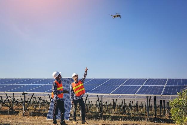Elektrische en instrumenttechnicus vliegende drone naar onderhoud elektrisch systeem op zonnepaneelveld