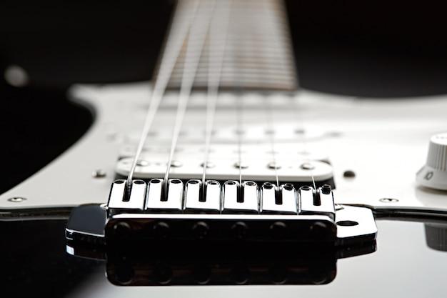 Elektrische gitaar, focus selectie op snaren, zwarte top op achtergrond, niemand
