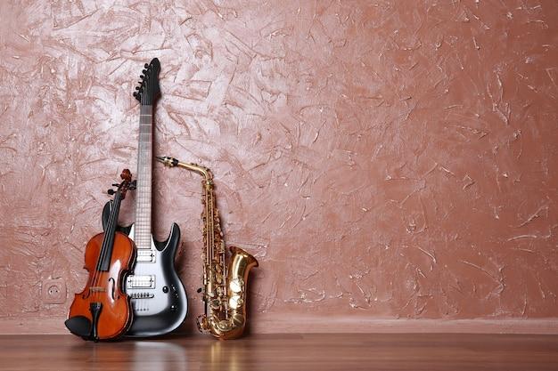 Elektrische gitaar, saxofoon en viool op bruine muur met exemplaarruimte
