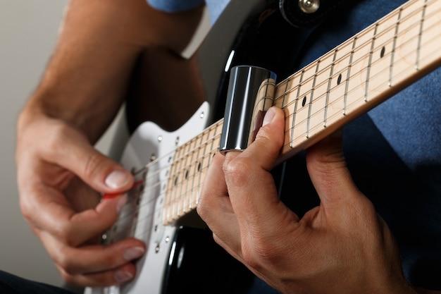 Elektrische gitarist die lied met schuifregelaar uitvoert