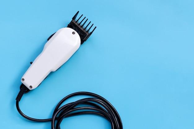 Elektrische haarclipper op blauwe achtergrond.