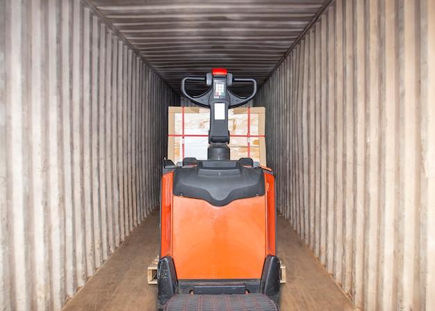 Elektrische heftruck palletkrik laadt vrachtpallet in vrachtcontainer vrachtverzending levering vrachtvrachtwagen