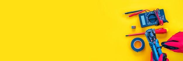 Elektrische installatie meetinstrumenten tools op een gele achtergrond met kopieerruimte. plaats voor tekst.