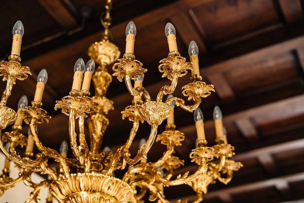 Elektrische kroonluchter met bollen antieke gouden kroonluchter in het interieur van een oude villa
