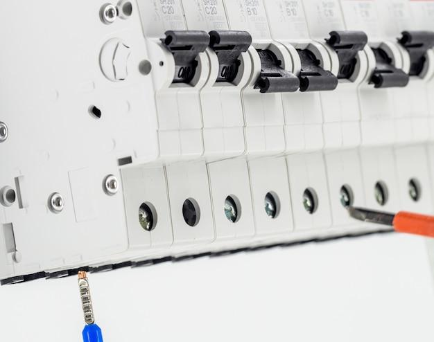 Elektrische machines, schakelaars, geïsoleerd op wit, close-up, sluit markeringskabel aan op een apparaat met een rode schroevendraaier