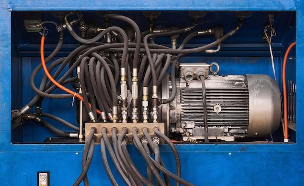 Elektrische motorpomp en regelkleppen met slangen van een hydraulische machine close-up