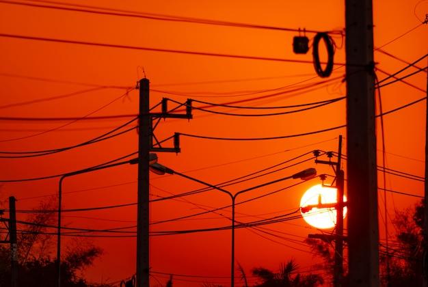 Elektrische paal en transmissielijnen in de avond. elektriciteitsmasten met draadkabel en straatlantaarnpost bij zonsondergang. kracht en energie in landelijke stad. mooie rode zonsonderganghemel achter elektrische polen.