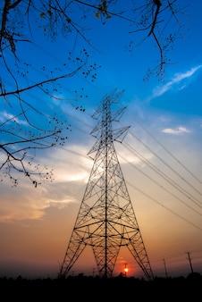 Elektrische palen en lijnen in de schemering of hoogspanningstorens bij mooie hemel