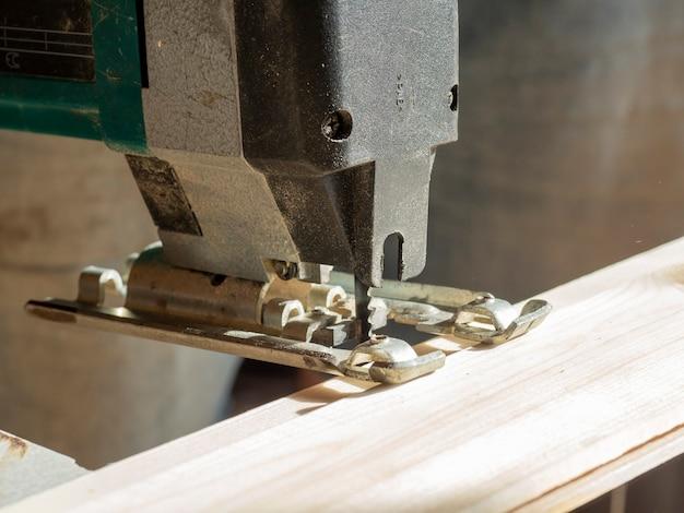 Elektrische puzzel die een houten plank gaat snijden. close-up van het mes. selectieve focus