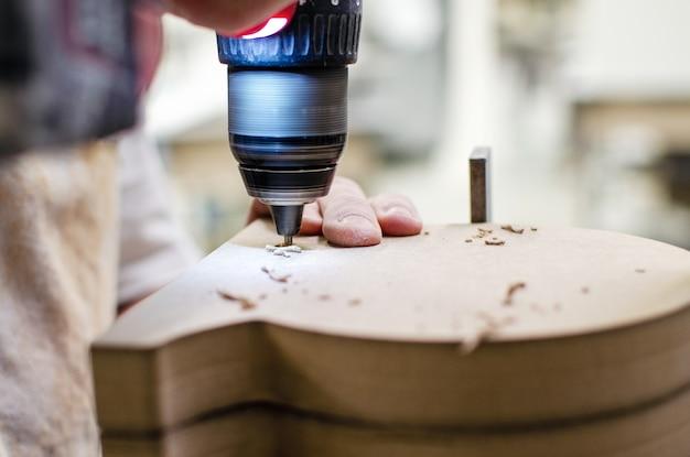 Elektrische schroevendraaier. een timmerman werkt met een handgereedschap op een werktafel. close-up bekijken.