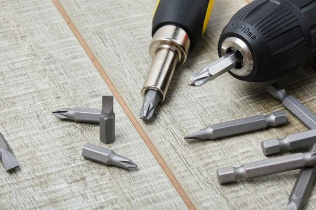 Elektrische schroevendraaier, zelftappende schroeven, schroevendraaierbits, gereedschapskist op een houten oppervlak kopie ruimte
