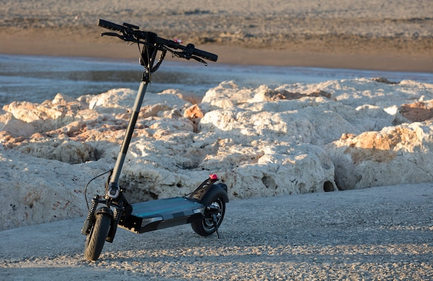 Elektrische scooter bij het strand bij zonsondergang