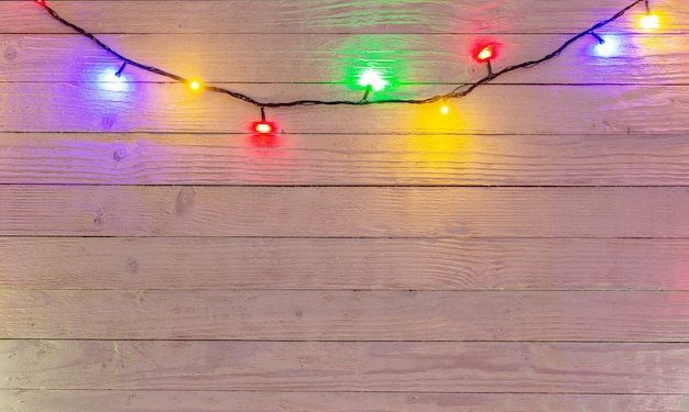 Elektrische slinger met veelkleurige gloeilampen op een houten oppervlak, kerstverlichting