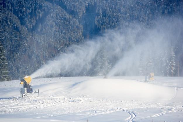 Elektrische sneeuwmachine die kunstsneeuw op berghelling sproeit. voorbereiding voor opening nieuw skiseizoen.