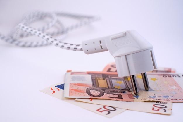 Elektrische stekker op eurobankbiljetten. conceptueel beeld over de stijgende energiekosten