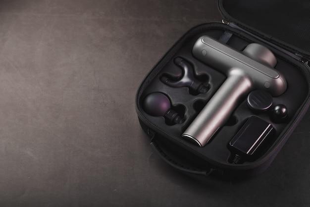 Elektrische stimulator machine voor lichaamsmassage in een geval op een zwarte achtergrond.
