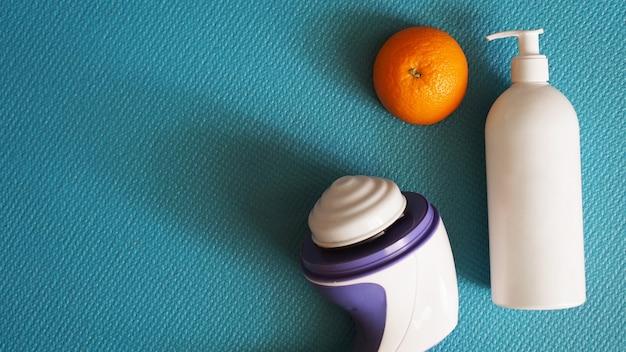 Elektrische stimulator voor cellulitis. lotion, sinaasappel en anti-cellulitis massage stimulator op een blauwe achtergrond