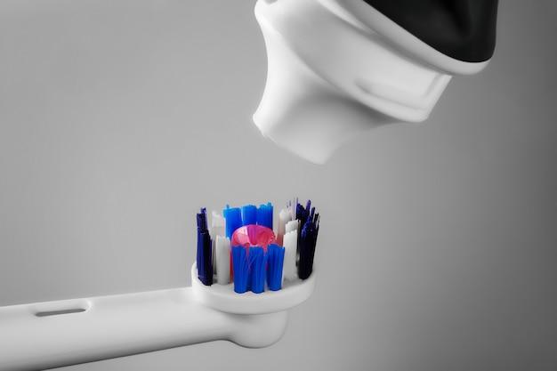 Elektrische tandenborstel en tandpasta op lichte achtergrond geïsoleerd op lichte achtergrond met kopie ruimte voor tekst.