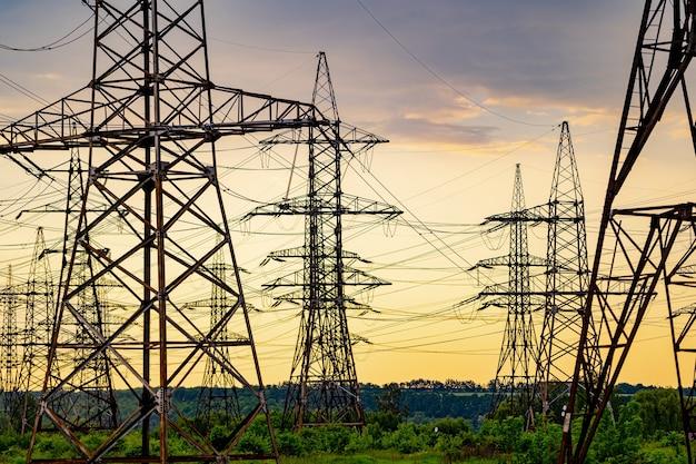 Elektrische transmissielijnen over groen gras. hoogspanningslijnen in het prachtige landschap van de natuur. selectieve aandacht.