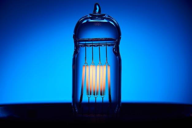 Elektrische vintage edison gloeilamp met een spiraal op een blauwe achtergrond