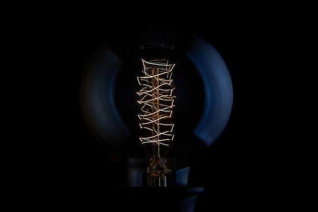 Elektrische vintage edison gloeilamp met een spiraal op een zwarte achtergrond