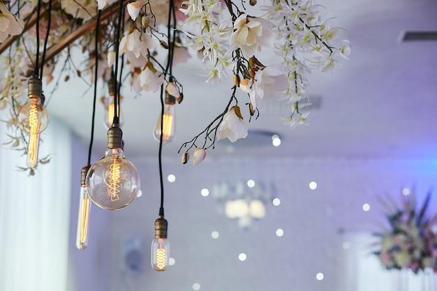 Elektrische vintage gele gloeilampen en verse bloemen