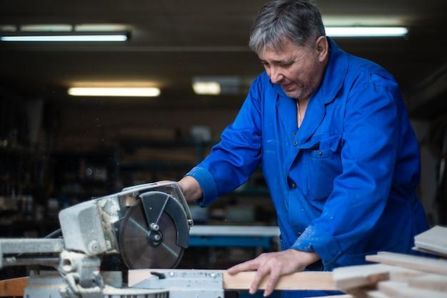 Elektrische zaag voor het zagen van planken, de werknemer zaagt een houten plank in de werkplaats