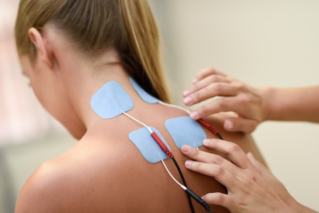 Elektro stimulatie in fysiotherapie aan een jonge vrouw