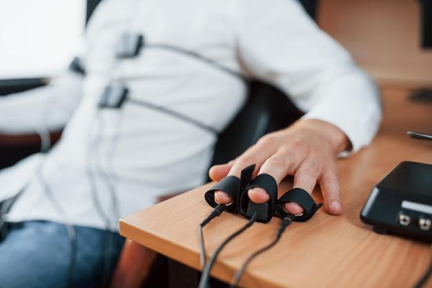 Elektroden op vingers. verdachte man passeert leugendetector op kantoor. vragen stellen. polygraaftest