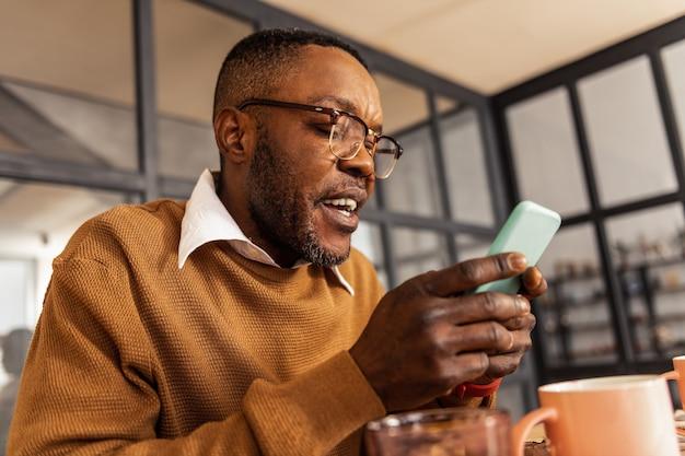 Elektronisch apparaat. aardige knappe man met behulp van zijn moderne smartphone tijdens het online chatten