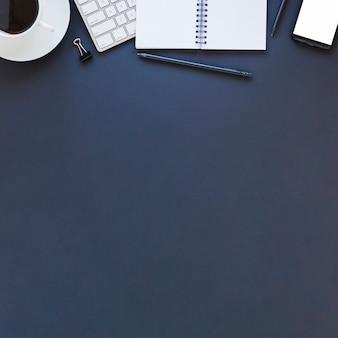 Elektronisch apparatennotitieboekje en koffiekop op donkerblauwe lijst