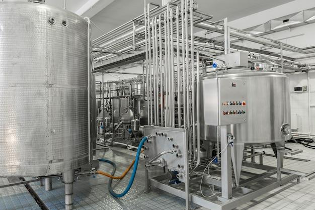 Elektronisch bedieningspaneel en tank in een melkfabriek. apparatuur in de zuivelfabriek