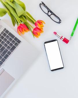 Elektronische apparaten in de buurt van bloemen, lippenstift en glazen