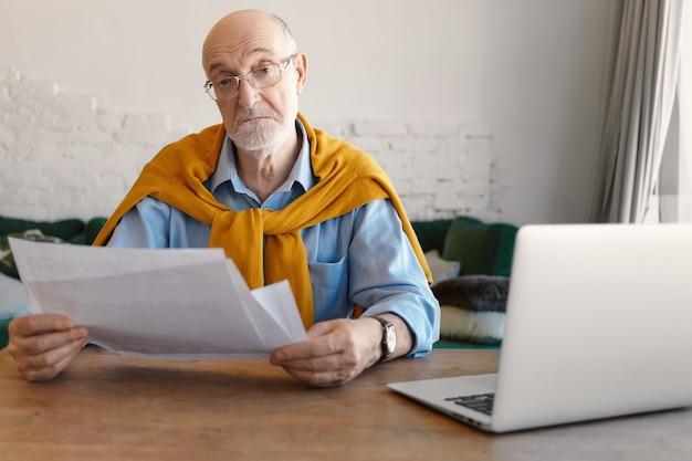 Elektronische gadgets, papierwerk, mensen, beroep en levensstijlconcept. foto van stijlvolle kale volwassen man met witte baard zaken op afstand beheren, papieren lezen, met behulp van laptopcomputer