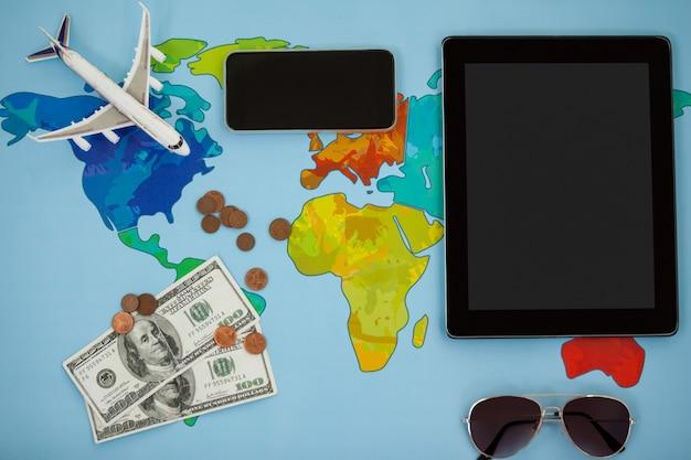 Elektronische gadgets, zonnebril, dollar en vliegtuigmodel