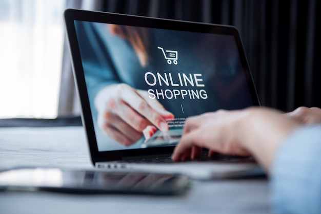 Elektronische handel en online het winkelen concept, vrouwenhand die laptop (modelwebsite) met behulp van en creditcard houden om online betaling online te winkelen.