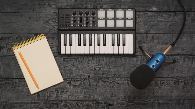 Elektronische muziekmixer en draadmicrofoon op een zwarte houten lijst.