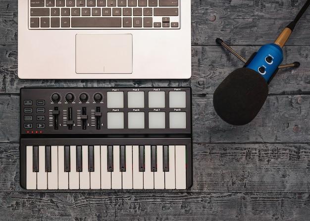 Elektronische muziekmixer, laptop en draadmicrofoon op een zwarte lijst