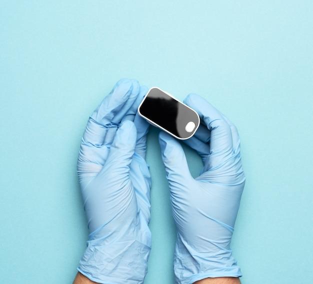 Elektronische pulsoximeter in de handen van een arts, die blauwe latexhandschoenen draagt, close-up