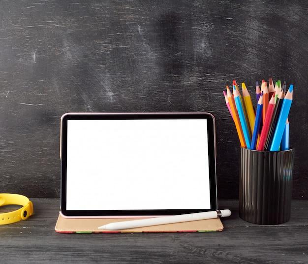 Elektronische tablet met een leeg wit scherm en multi gekleurde houten potloden