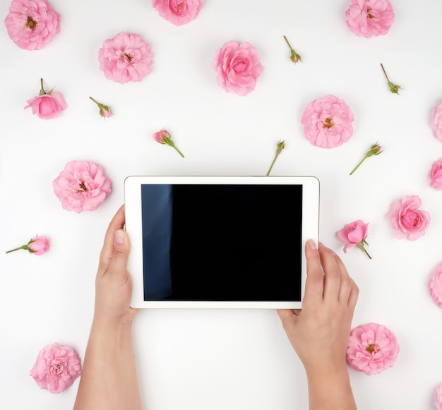 Elektronische tablet met een leeg zwart scherm en twee vrouwelijke handen die apparaat vasthouden