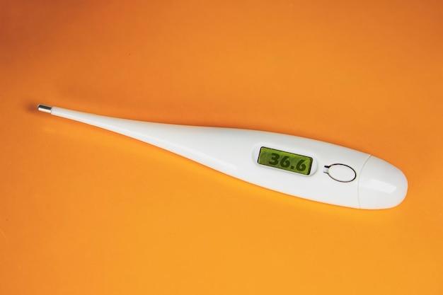 Elektronische thermometer op oranje achtergrond plat lag bovenaanzicht kopieerruimte. bescherming tegen virus, coronavirus, griep, verkoudheid, ziekten. medisch hulpmiddel, concept van gezondheid. allergie seizoen.