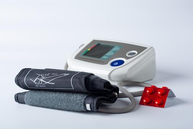 Elektronische tonometer op een witte achtergrond met pillen